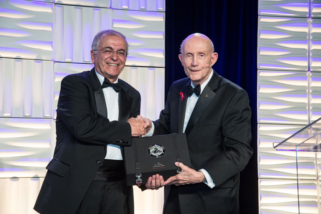 Thomas Stafford presents the OMEGA speedmaster watch to Dr. Charles Elachi